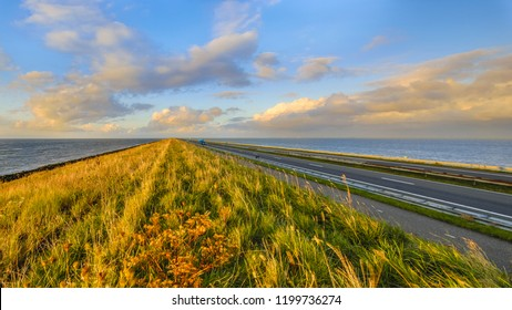 Afsluitdijk dutch dike with motorway and cycling track during  sunset with clouded sky