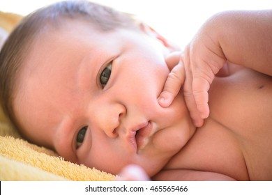 After childbirth newborn baby lay in a bed with a diaper