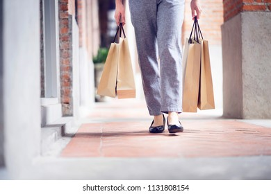 After day shopping. Close-up of young woman carrying shopping bags while walking along the street.Woman holding shopping bags.Consumerism,lifestyle concept.