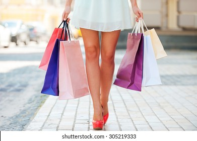 After day shopping. Close-up of young woman carrying shopping bags while walking along the street