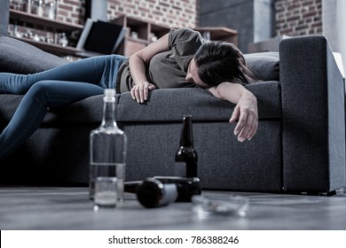 After drinking. Sleepy drunk young woman lying on the sofa and sleeping with empty bottles standing on the floor in front of her