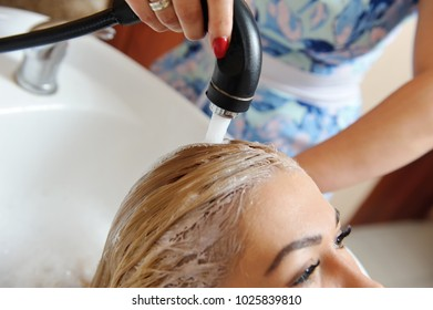 After dyeing hair, the hairdresser washes the girl's hair and washes off the shampoo