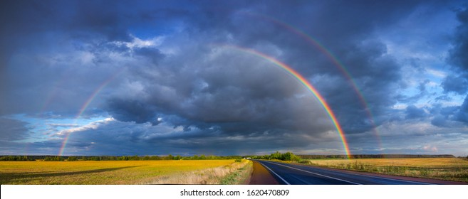 After an evening summer showers. A bright rainbow stands over the highway. Trucks and passenger cars go on the wet asphalt. Real photo - montage or graphic software was not used.