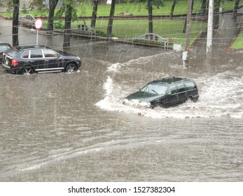 After heavy rain there is a flood on the city roads. The car hardly rides in the water to the level of the hood