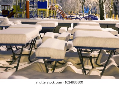 After a heavy snowfall, the fabulous beauty of the morning winter old park in Europe, Ukraine among the beautiful white trees are carousels, slides, attractions for children and parents