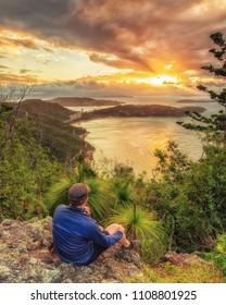 After a hike up Passage Peak on Hamilton Island, a walker rests and watches the sunset