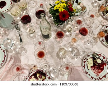 After a long and elegant dinner, a table with white tablecloth is full of empty and half-empty wine glasses and half-eaten desserts.