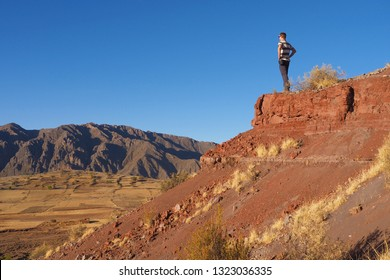 After a long hike, a young man reaches a beautiful view point in the Maragua Crater in Bolivia and enjoys the view over the lonely land below.