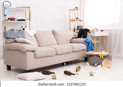 After party. Chaos and mess in room, clothes, food and bottles on the floor and sofa, copy space