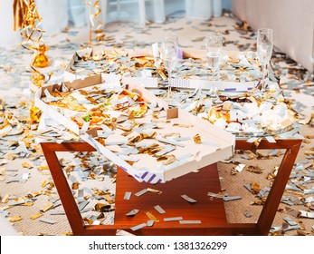 After party chaos. Messy room. Floor and table with pizza and champagne glasses covered with confetti. Celebration leftovers.
