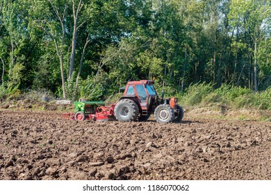After plowing the field the peasant makes the field ready for sowing. The green colored cultivator and crumbling tool is mounted on the red colored tractor. The field is on the edge of a Dutch forest.