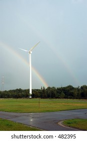 After the rain, a rainbow with energy windmill in front.