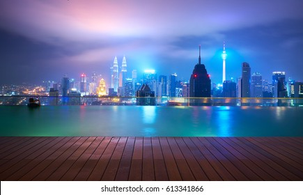 After the rainy night, in the roof top of the swimming pool, visitors swim while enjoying beautiful city skyline view ,Kuala lumpur, Malaysia.