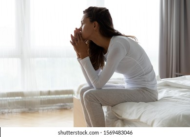 After sleepless night sad woman got up sit on bed thinking, lost in sad thoughts about irreparable mistake decision about abortion, feeling remorse, break up in relations, divorce and jealousy concept