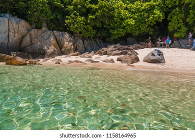 After a snorkelling trip, tourists are eating at the rocky part of Rawa beach under the shade of trees, while the fishes are swimming in the shallow part of the island which is near Perhentian Kecil.