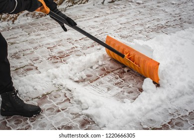 After a snowfall, a man clears snow from the road in winter, work in the winter season.