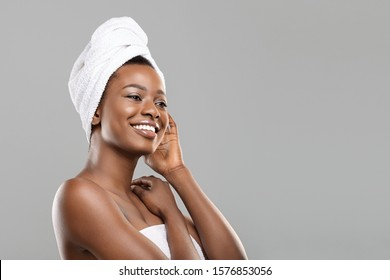 After Spa. Beautiful african woman with bath towel on head and perfect glowing skin looking aside relaxed after beauty treatment, grey background