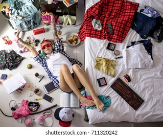 after studying blonde student, lying on the floor in headphones and sunglasses, stretches, listening to music The image of a modern student, education. Accessories of a modern young girl