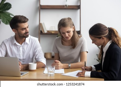 After successful job interview mixed race female candidate was hired for position signing employment agreement. Businesspeople sitting at desk finishing negotiations affirm contract with signature