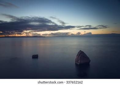 After sundown dusk over stony seascape, long exposure image