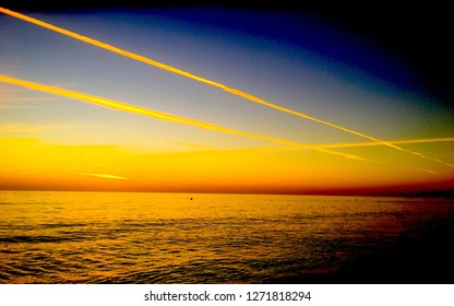 AFTER SUNSET CONTRAILS IN SKY OVER SEA