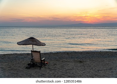 after sunset, everybody going to home and empty sunlounger standing at the beach with umberella