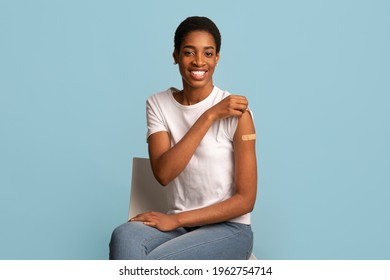 After Vaccination Concept. Portrait Of Vaccinated Black Woman Showing Arm After Coronavirus Vaccine Injection, Positive Lady Sitting With Rolled Up Sleeve Over Blue Background, Smiling To Camera