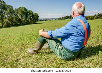 After work, a farmer sits in the meadow and looks down on his mowed meadow valley on a wonderful sunny afternoon in the summer.