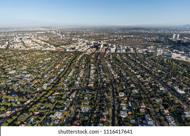 Afternoon aerial view of Beverly Hills streets with mid Wilshire and downtown Los Angeles California in background.