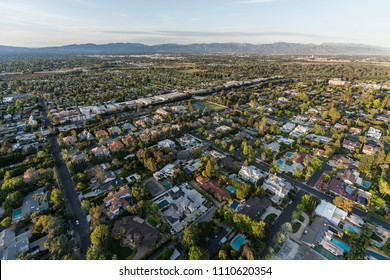 Afternoon aerial view of Encino homes and streets in the San Fernando Valley area of Los Angeles, California.