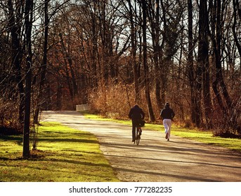 afternoon backlight in a sunny December day at Englischer Garten in Munich, a biker and a runner
