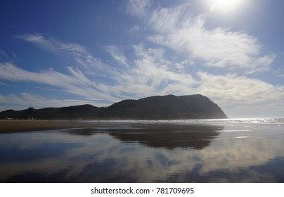 Afternoon sun dramatically breaks through clouds behind Tilamook Head, with reflections on beach, Seaside, Oregon coast