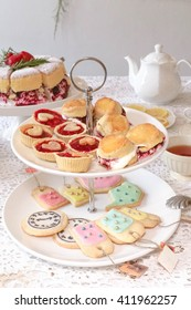 Afternoon Tea. Cakes, scones and sugar cookies served on on two tiered tray. selective focus