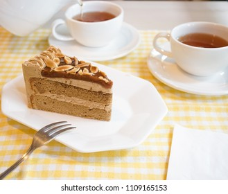 Afternoon tea. Coffee cake serves with cup of teas. Blurred teapot is pouring tea on the background.