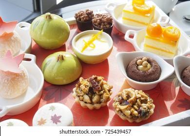 afternoon tea dessert set with financier cake, yuzu macaron, yuzu pudding,yuzu scone, orange cream mochi, orange cake, caramel chocolate glazed with crispy rice and peanut tart.