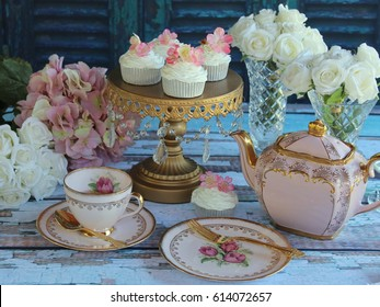 Afternoon Tea with Vintage Pink Tea cups, Teapot, gold cake stand and cupcakes on a distressed wood table.