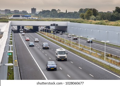 Afternoon traffic on A4 motorway near The Hague Randstad area. Highway crossing aquaduct tunnel with urban area of Rotterdam in backdrop, Netherlands.