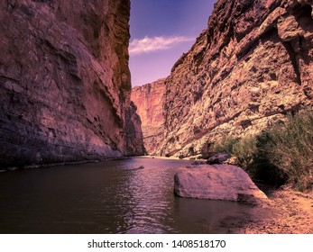An afternoon view of the Santa Elena Canyon, with a purple tint. A canoe can be seen in the distance.