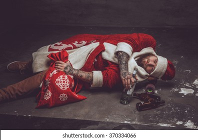 Afterparty drunk man in Santa's clothes lying on a floor.