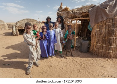 Agadez, Niger - September 2013: African  family Djerba tribe in traditional colorful clothes in front of their house in Sahara desert on the boarder of Niger and Algeria