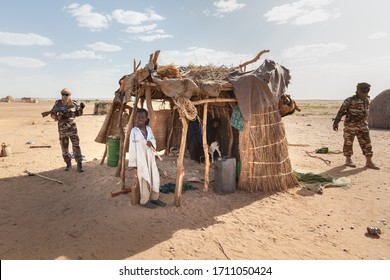 Agadez, Niger - September 2013: military guard soldiers and African boy  traditional clothes in front of cattle shelter  in Sahara desert on the boarder of Niger and Algeria