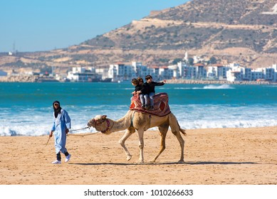 AGADIR - JAN 03: Camel with tourists in Agadir on January 03. 2018 in Morocco