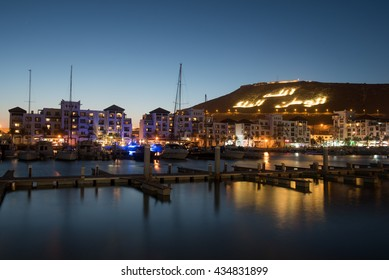 Agadir marina at night with mountain on the background with inscription: Allah, The King, Native Land, Morocco