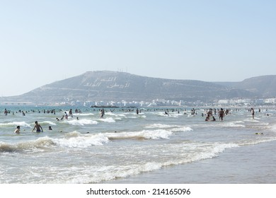 AGADIR, MOROCCO - AUGUST 22: Beautiful beach full of vacationing people on 22 August 2014 in Agadir, Morocco. Kasbah mountain in the background with inscription: Allah , The King , One's native land.
