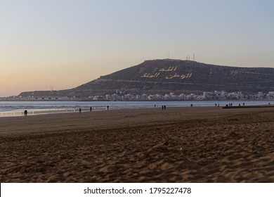 Agadir, Morocco beach with Moroccan motto on the mountain. Writing on the hillside meaning, God, Country, King. Evening sunset with people walking on the beach.