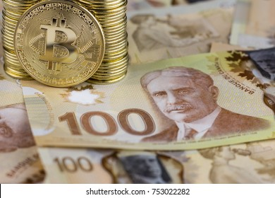 Agadir / Morocco - November 10 2017 : A stack of hundred dollar bills. Canadian dollars. Close up.  Bitcoin. Digital Currency. Column of coins. Illustrative editorial.