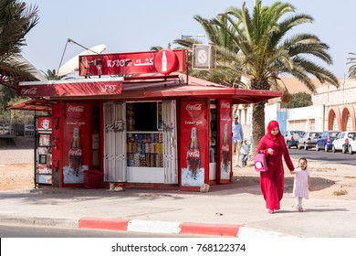 Agadir, Morocco, October 23, 2017: Muslim mother in red hijab walks past red Coca Cola kiosk.