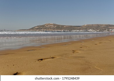 Agadir, Morocco.Feb.3,2019:Beach with tourist walking and Moroccan motto on the mountain. Writing on the hillside meaning, God, Country, King. People walking on the beach footsteps in the sand.