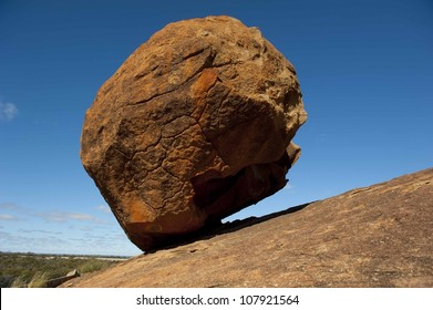 Against all odds, gravity or not, big boulder balancing on steep rocky hill, isolated with blue sky as background and copy space.