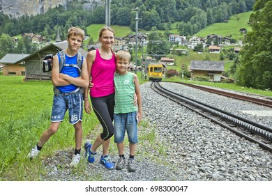 Against the background of the approaching train. Mother and two children are traveling along the path to the outskirts of Lauterbrunnen, Switzerland.